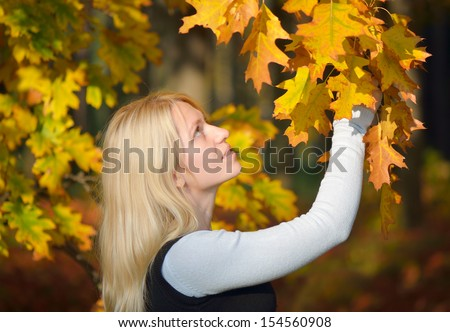 Blonde girl in the autumn park admiring branch autumn leaves of oak - stock photo