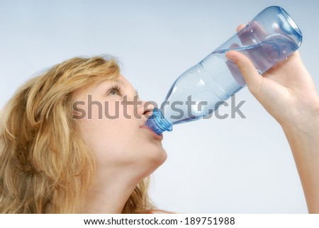 Blonde girl is drinking from a bottle.