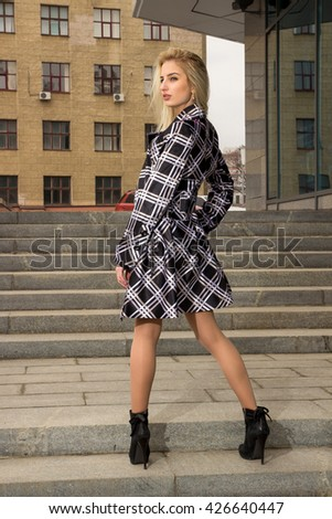 Blonde girl is staying on stairs and looking back