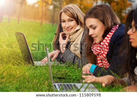 blonde girl laying with laptop with friends - stock photo