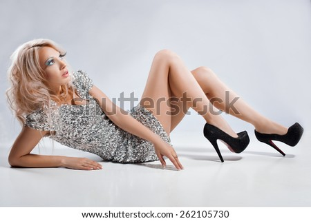 Blonde girl lies on a white background. She has long eyelashes, eyes looking up. Her silver dress. - stock photo