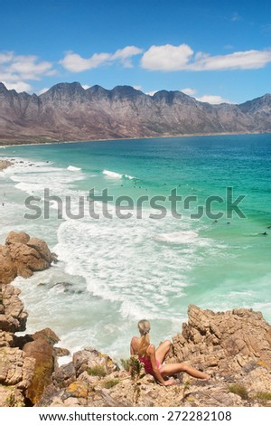 Blonde girl looks at the majestic beach. Shot near Strand/Cape Town, Western Cape, South Africa.  - stock photo