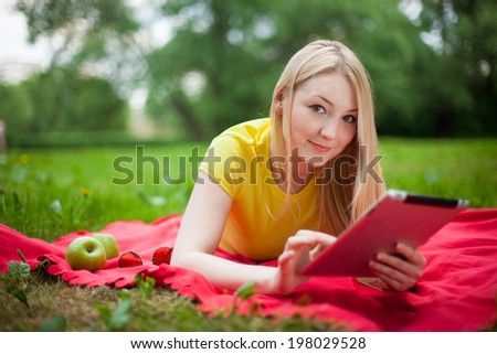blonde girl lying in the park with tablet on the red coverlet. summer  - stock photo