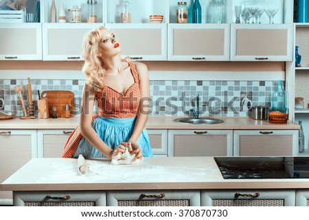Blonde girl on kitchen kneads dough. Next to the stove, it cooks. - stock photo