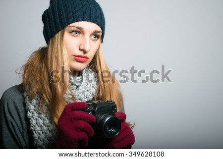 blonde girl photographed in vintage camera, Christmas and New Year concept, studio photo isolated on a gray background