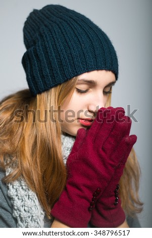 blonde girl praying religion theme, dressed in winter clothing, Christmas and New Year concept, studio photo isolated on a gray background