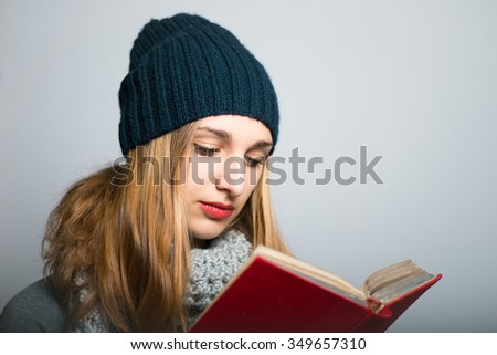 blonde girl reading a book, dressed in winter clothing, Christmas concept, studio photo isolated on a gray background
