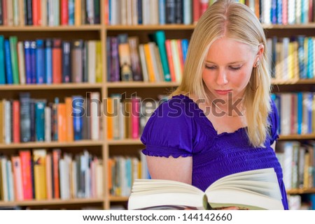 Blonde girl reading a book in front of bookcase