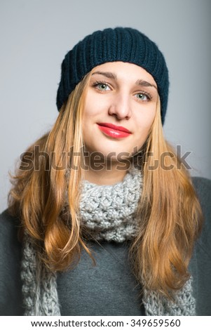 blonde girl remembered something, dressed in winter clothing, Christmas concept, studio photo isolated on a gray background - stock photo