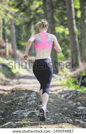 Blonde girl running in the forest