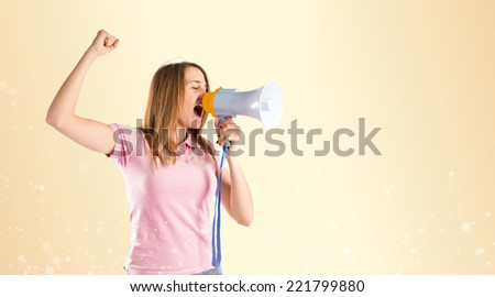 Blonde girl shouting with a megaphone over gloss background  - stock photo
