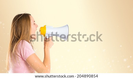 Blonde girl shouting with a megaphone over ocher background  - stock photo