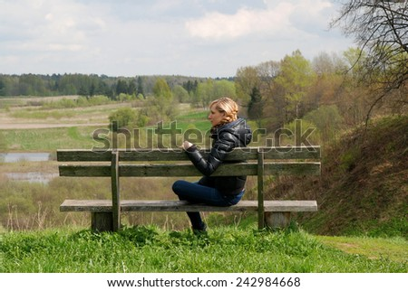 Blonde girl sitting on a bench alone in park