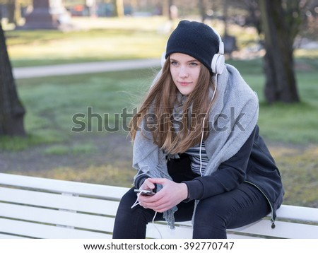 blonde girl sitting on a park bench listening to music
