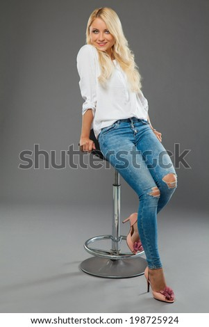 blonde girl sitting on the chair wearing jeans and white shirt in the studio - stock photo