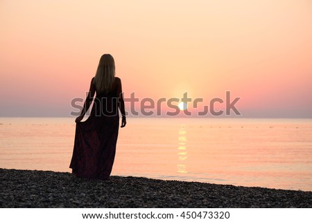 Blonde girl standing on the beach. Beautiful sunrise. Activities at the resort. Sea vacation. Turkey