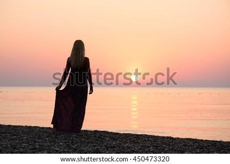 Blonde girl standing on the beach. Beautiful sunrise. Activities at the resort. Sea vacation. Turkey - stock photo
