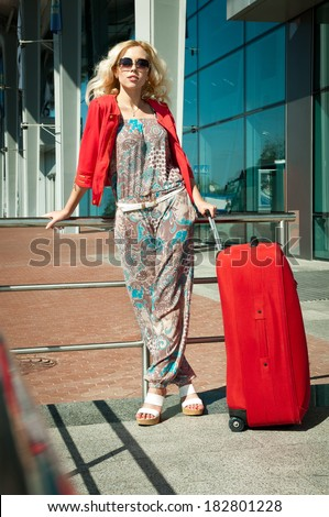 blonde girl standing with a suitcase near the station - stock photo