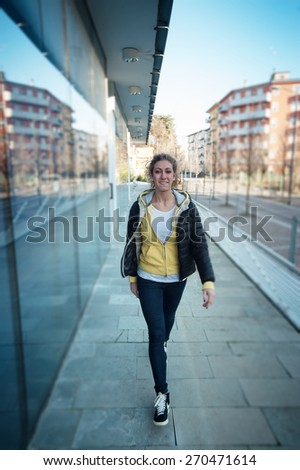 Blonde girl walking down the street - stock photo