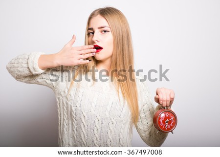 blonde girl wants to sleep with an alarm clock, isolated - stock photo