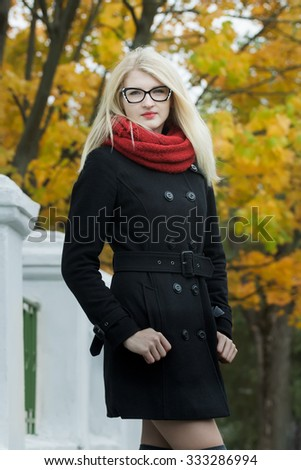 Blonde girl wearing black and white cat eye glasses is posing on autumn city street with thumbs in pocket