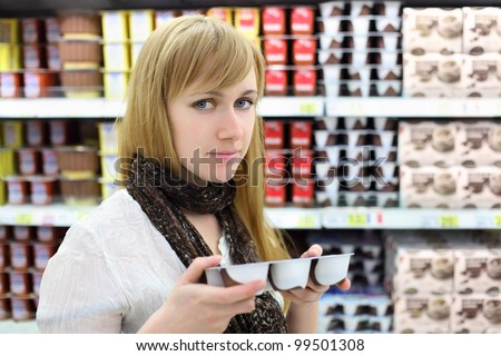 Blonde girl wearing scarf chooses yoghurt in store; shallow depth of field - stock photo