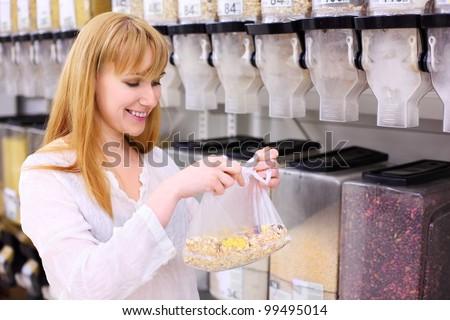 Blonde girl wearing white shirt chooses muesli in store; shallow depth of field - stock photo