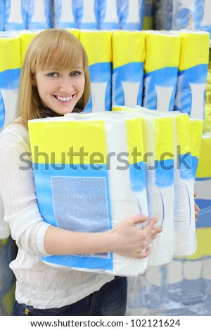 Blonde girl wearing white shirt holds big pack of toilet paper in shop; shallow depth of field - stock photo