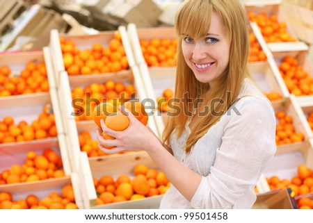Blonde girl wearing white shirt holds oranges in store; shallow depth of field - stock photo