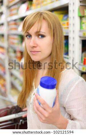 Blonde girl wearing white shirt keeps salt in store; shallow depth of field - stock photo