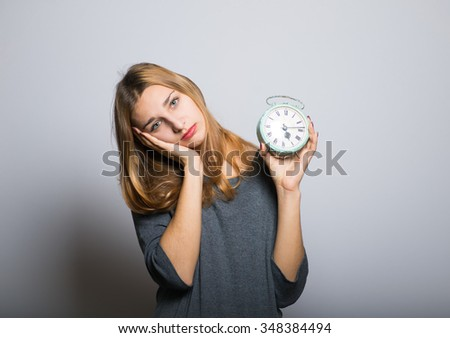 blonde girl with an alarm clock in hands, with clean skin, lifestyle concept studio photo isolated on a gray background - stock photo