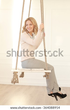 Blonde girl with curly hair sitting on the swing