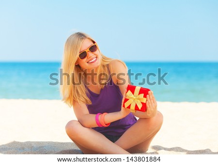 Blonde girl with gift at the beach. - stock photo