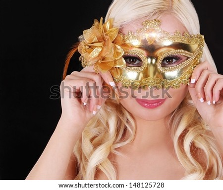 Blonde girl with gold carnival mask over black background. Masquerade. Halloween - stock photo