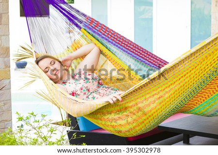 Blonde girl with long hair lounging in hammock outdoors