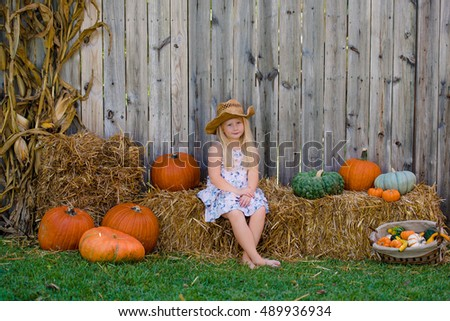 Blonde girl with long hair sitting on the hay with pumpkins fall decorations