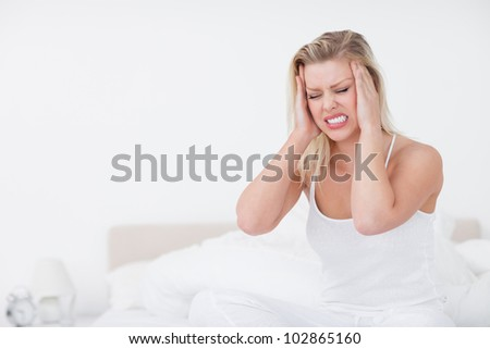 Blonde grimacing while having a headache on her bed - stock photo