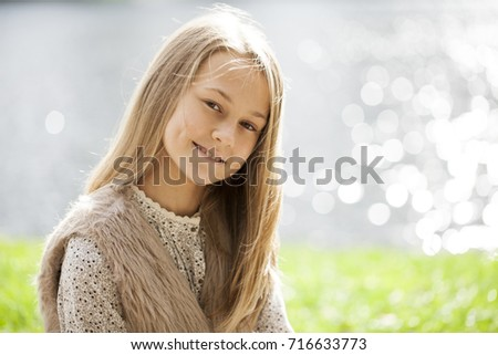 Blonde Hair Beauty. Portrait of a beautiful little girl on the background of summer street