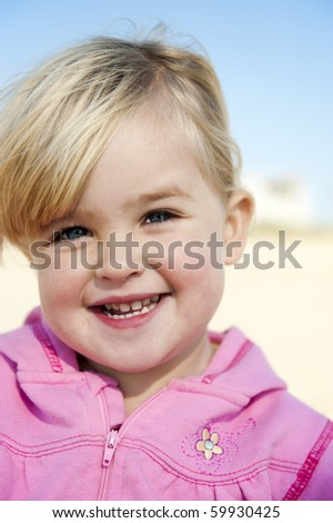 Blonde hair, blue eyes, pink top. Gorgeous portrait of a 2 year old child - stock photo