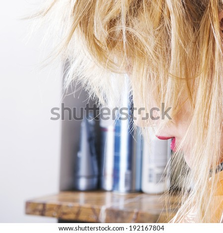 Blonde hair client in a hairdressing salon - stock photo