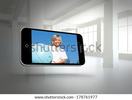 Blonde happy boy on smartphone screen against white room with windows
