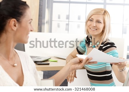 Blonde happy casual businesswoman working with colleague at office, smiling, handing over paperwork.