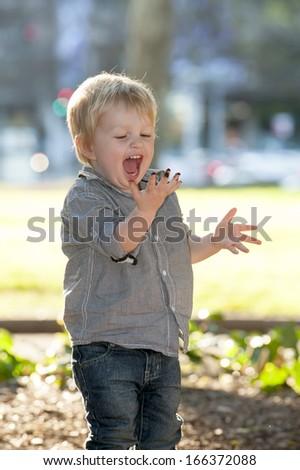 Blonde Happy Child with mud stained hand playing in the Park - stock photo