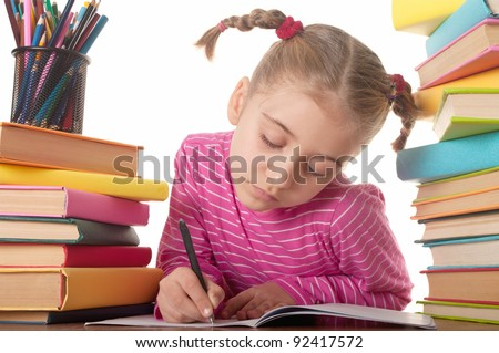 Blonde happy schoolgirl works on her homework, write something in her notepad
