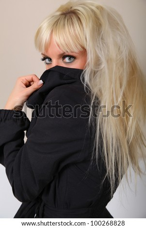 blonde hides her face in the collar - stock photo