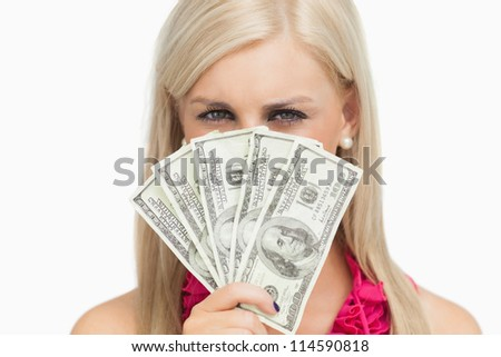 Blonde hiding her face with 100 dollars banknotes against white background
