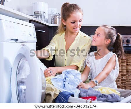 Blonde housewife and little girl doing laundry together at home - stock photo