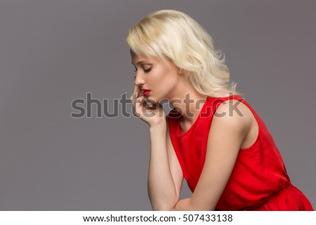 blonde in a red dress on a gray background