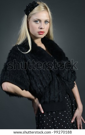 Blonde in black fur cape and black skirt - stock photo