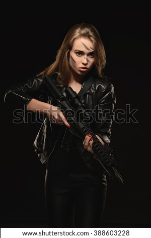 Blonde in black taking aim with a rifle. Photographed in studio on a black background